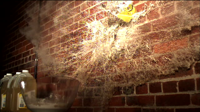 a beverage splashes as its container smashes against a brick wall. - jug stock videos & royalty-free footage