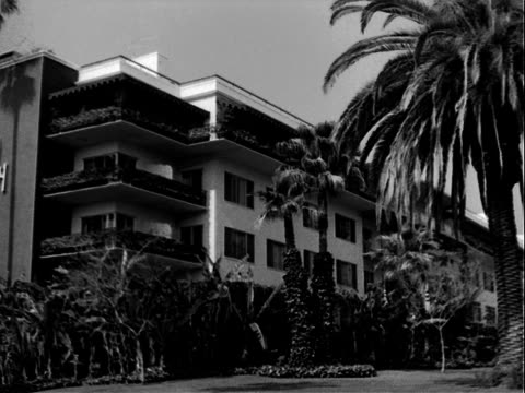 beverly hills hotel surrounded by palm trees / 'beverly hils hotel' sign on facade. beverly hills hotel on january 01, 1950 in california - beverly hills hotel stock videos & royalty-free footage
