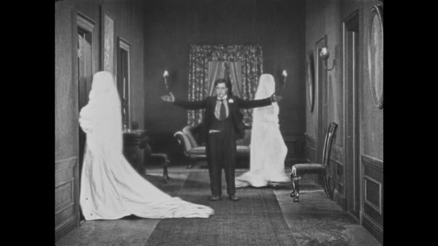 1921 bewildered man (buster keaton) decides to direct bedsheet ghosts like traffic - spettrale video stock e b–roll