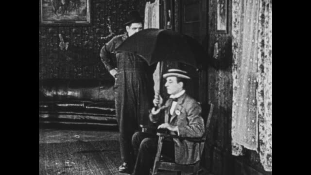 1925 a bewildered man (oliver hardy) watches nonchalant man open umbrella indoors and walk away - slapstick comedy stock videos & royalty-free footage