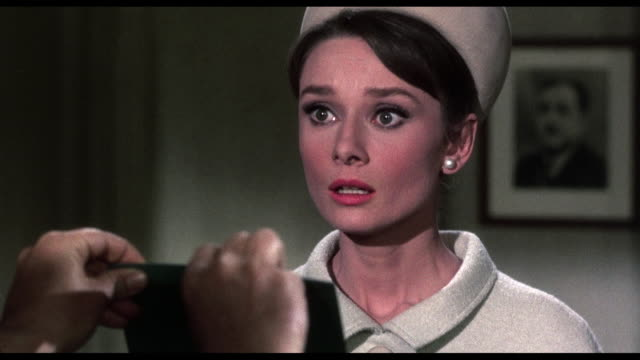 1963 Bewildered woman (Audrey Hepburn) stares as detective (Jacques Marin) holds out numerous passports belonging to her dead husband