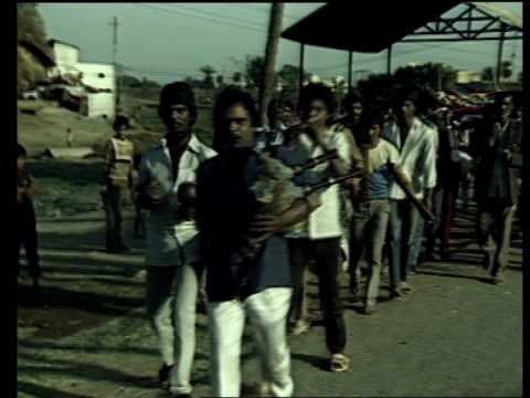 stockvideo's en b-roll-footage met 301188/nao india bhopal street as motor cyclist along in bv sun rises in sky cms side woman pumping water as others stand around cs child peeps round... - bhopal