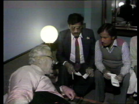 INDIA Madhya Pradesh Bhopal American lawyer Melvin Belli talking to victims' representatives in his hotel room MS Belli lying on bed as speaks with...