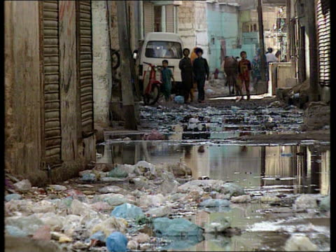bhutto under pressure pakistan karahi lyari shacks built by river pull out with animals next narrow street with open sewer running down middle bags... - air traffic control点の映像素材/bロール