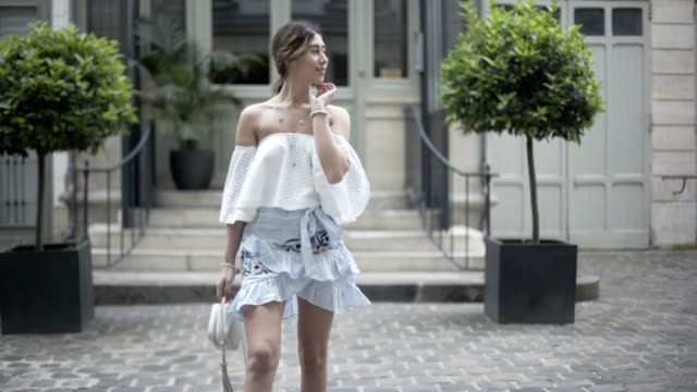 bianca derhy, fashion blogger bibi goes chic, wears a revolve off shoulder lace top, a shein blue ruffled flower print skirt, a furla bag, and black... - skirt stock videos & royalty-free footage