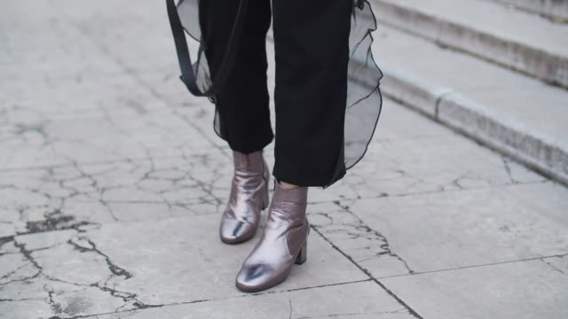 Bianca Derhy fashion blogger from Bibi Goes Chic wears a white top with flared sleeves black pants with ruffles a pink bag and purple shiny boots...
