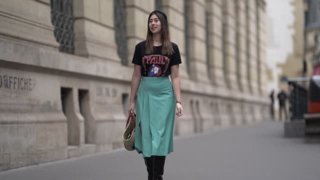 stockvideo's en b-roll-footage met bianca derhy wears a headband a tshirt with a patch a turquoise skirt black leather boots a paul joe straw bag outside paul joe during paris fashion... - haarband