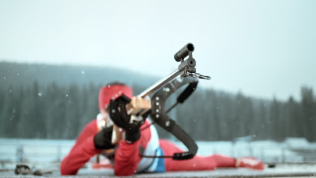 slo mo biathlete aiming at the target in prone position - biathlon stock videos and b-roll footage