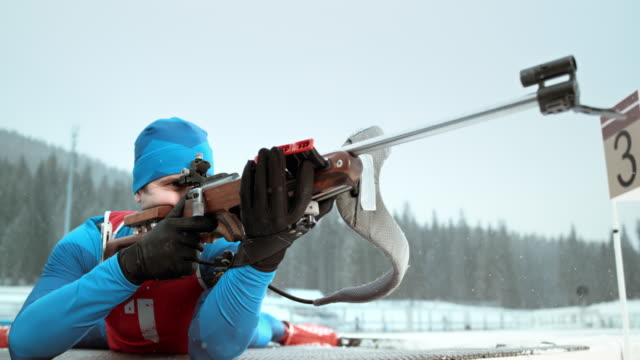 vídeos y material grabado en eventos de stock de slo mo biathlon athlete in prone position for the shot - biatlón