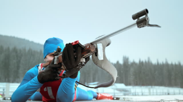 slo mo biathlon athlete in prone position to shoot - biathlon stock videos and b-roll footage