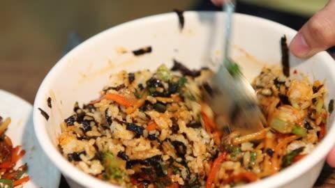 vídeos y material grabado en eventos de stock de bibimbap (mixed rice with vegetables, famous korean food) mixing with cockle - comida coreana