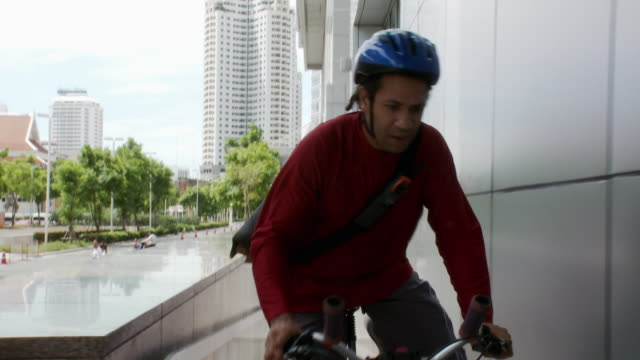 ms pov bicycle courier delivering envelope to office building, entering through door / bangkok, thailand - delivery person stock videos & royalty-free footage