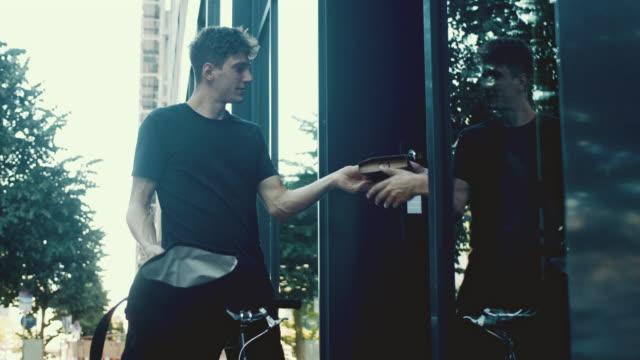お客様にパッケージを提供する自転車の宅配便 - 配達員点の映像素材/bロール