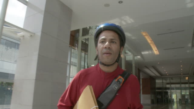 ms la pov bicycle courier talking through walkie talkie, walking in lobby / bangkok, thailand - delivery person stock videos & royalty-free footage