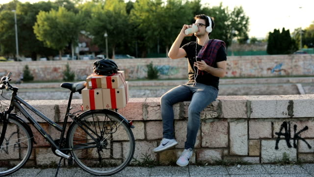 Bicycle delivery boy on a coffee break