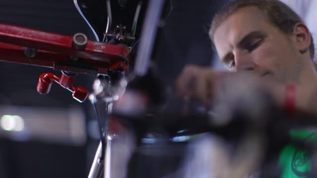 Bicycle mechanic twists 3-way Allen wrench in bike repair shop