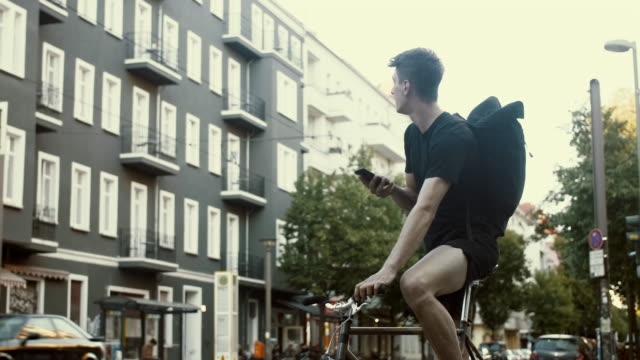 bicycle messenger looking for the address on the phone (slow motion) - delivery person stock videos & royalty-free footage
