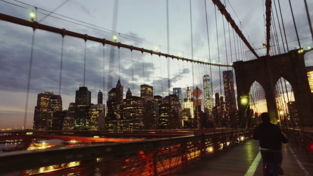 bicycle pov: night ride on the brooklyn bridge, ny city - ponte video stock e b–roll