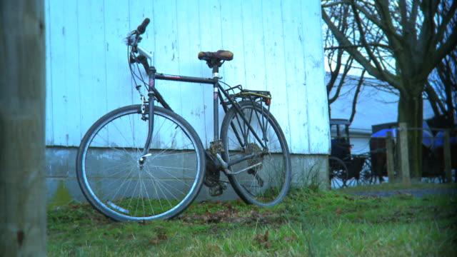 vídeos de stock, filmes e b-roll de bicicletas estacionadas contra amish barn - amish
