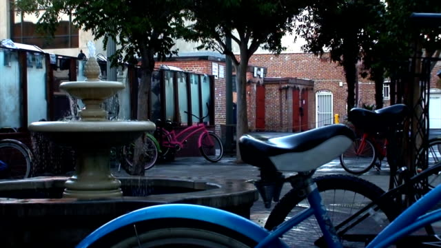 vídeos de stock, filmes e b-roll de estacionamento de bicicletas por uma fonte de água - antiquário loja
