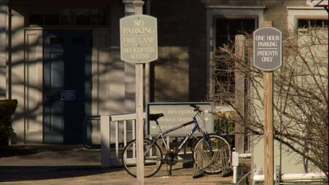 a bicycle parks near the entrance of a flight medic clinic. - no parking sign stock videos & royalty-free footage