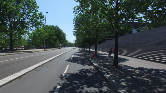 bicycle path and street with only three pedestrians and two cyclists. may 6, 2020 in paris, france. - road marking stock videos & royalty-free footage