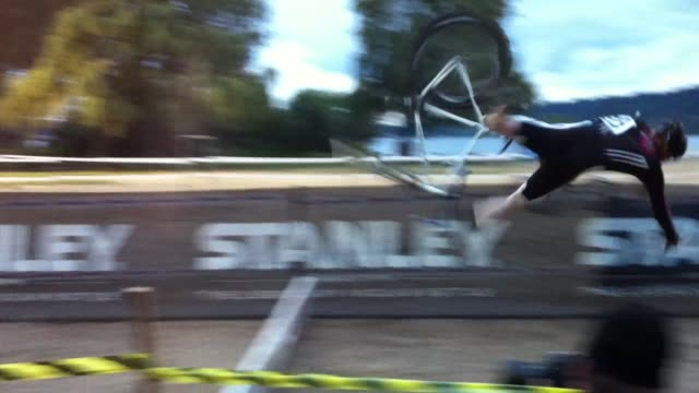 / bicycle race contestant tries to make jump over a wooden fence and goes head over heels and face plants into ground. man crashes bicycle during... - misfortune stock videos & royalty-free footage