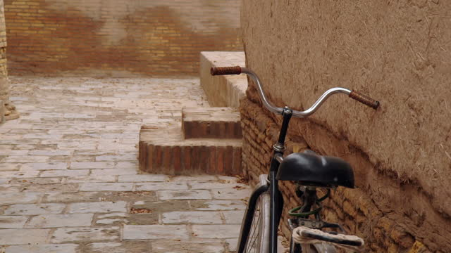 bicycle rests against wall - kopfsteinpflaster stock-videos und b-roll-filmmaterial