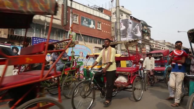 bicycle rickshaws auto rickshaws traffic and pedestrians move through a busy street in new delhi new delhi street scenes on february 22 2013 in new... - delhi stock videos & royalty-free footage