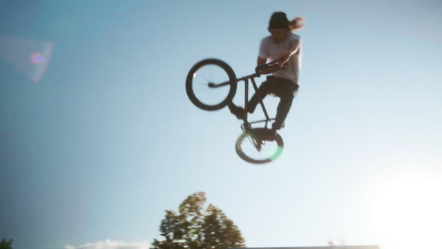 vídeos de stock, filmes e b-roll de cavaleiro da bicicleta de bmx em um parque do patim - termo esportivo