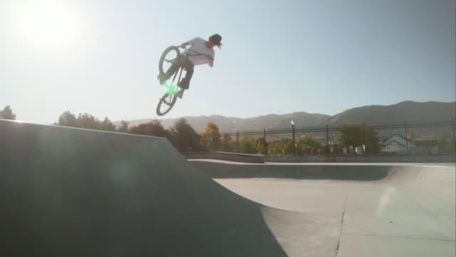 vídeos y material grabado en eventos de stock de bmx bicycle rider en un skate park - motociclista