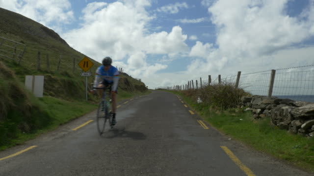 PAN L Bicycle rider on Slea Head Drive by Atlantic Ocean, Dingle Peninsula, Ireland