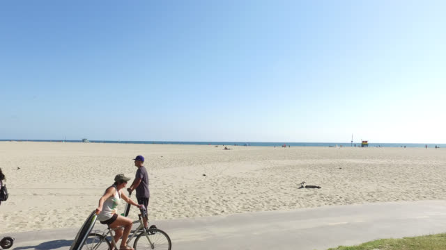 bicycle riders, electric kick scooter and joggers on beach promenade, venice, los angeles, california, usa - push scooter stock videos and b-roll footage