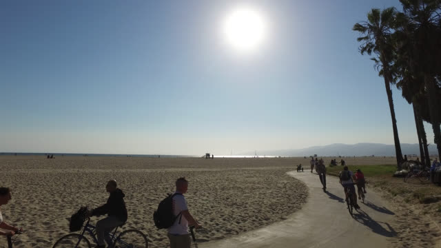 vidéos et rushes de bicycle riders, electric kick scooter and joggers on beach promenade, venice, los angeles, california, usa, against the light - scooter