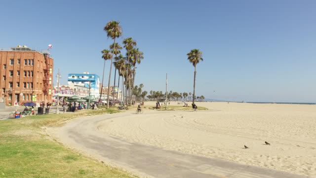 bicycle riders on beach promenade, venice, los angeles, california, usa - venice californie stock videos & royalty-free footage