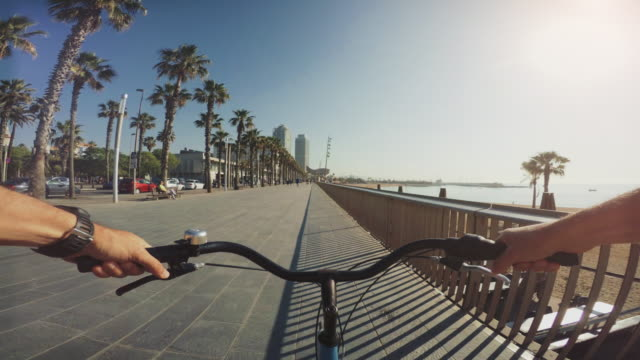pov bicycle riding at barceloneta beach in barcelona, spain - city break stock videos & royalty-free footage