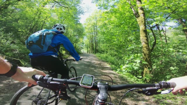 pov bicycle riding: biking together in the forest - wearable camera stock videos & royalty-free footage