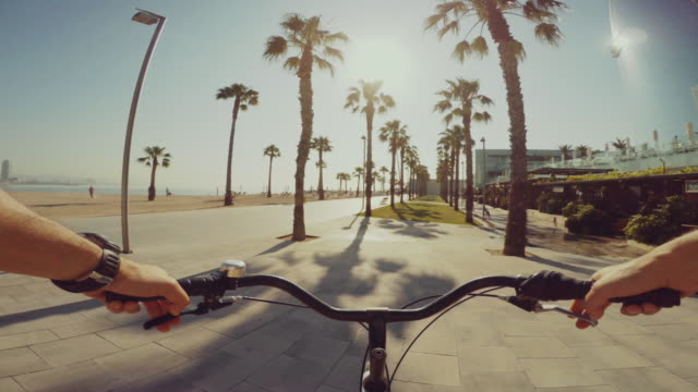 pov in bicicletta in spiaggia di barceloneta durante le vacanze estive - point of view video stock e b–roll