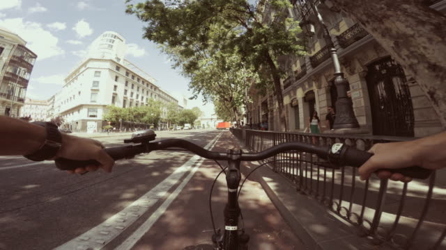 pov bicycle riding in the city life of madrid, spain - マドリード グランヴィア通り点の映像素材/bロール