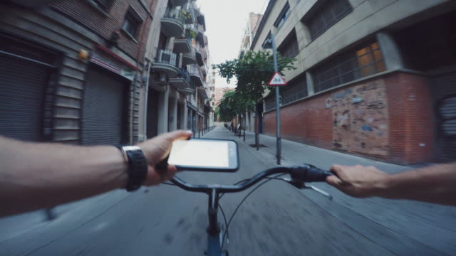 pov bicycle riding in the city, while consulting a map on mobile phone - city break stock videos and b-roll footage