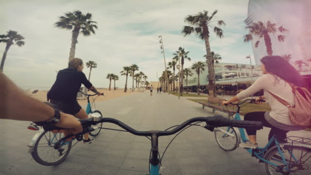 pov bicycle riding with friends at barceloneta beach in barcelona, spain - gente comune video stock e b–roll