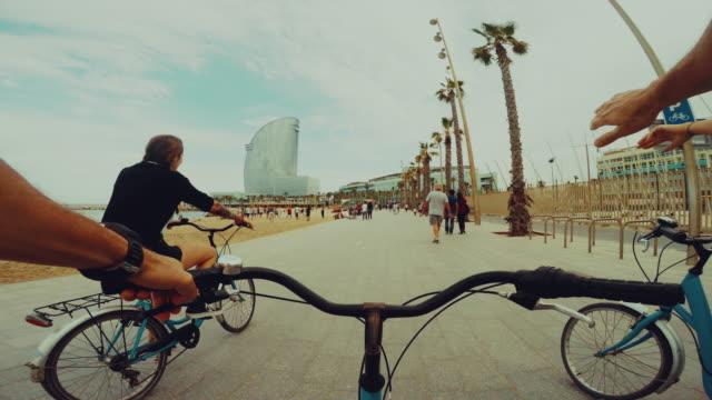 vídeos de stock e filmes b-roll de perspetiva pessoal bicicleta de equitação com raparigas: alto cinco e ir - porto de barcelona