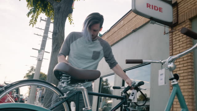 bicycle shop employees move bicycles onto sidewalk outside shop - eingang stock-videos und b-roll-filmmaterial