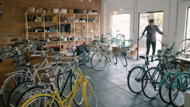 bicycle shop owner opens up shop in the morning - building entrance stock videos & royalty-free footage