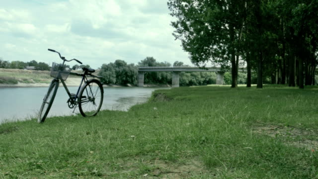 Bicycle standing on riverbank not far from the bridge
