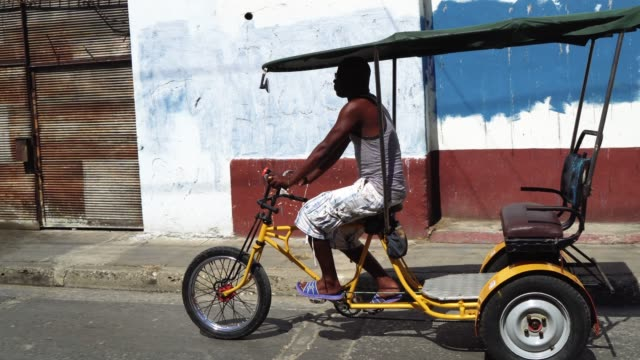 bicycle taxi driver with his vehicle, cuba - rickshaw stock videos and b-roll footage