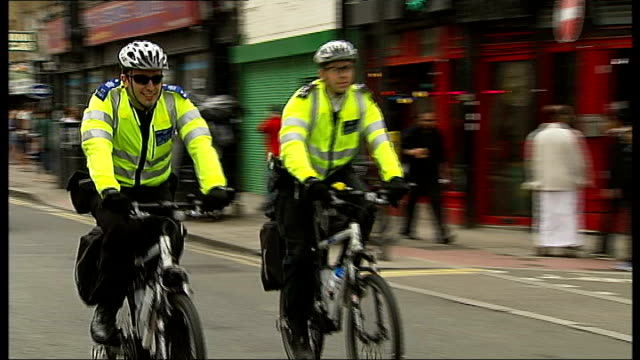 new police initiative in London ENGLAND London Brick Lane EXT Two police officers along street on bicycles Kulveer Ranger interview SOT Police...
