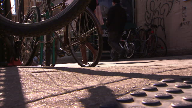 a bicycle tire and spokes spin near other parked bicycles. - speichen stock-videos und b-roll-filmmaterial