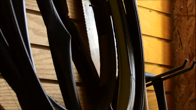 bicycle tires and inner tubes hang from a garage wall. - reifenschlauch stock-videos und b-roll-filmmaterial
