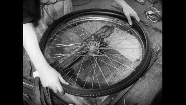 bicycle wheel has tyre fitted by hand in factory; 1952 - workbench stock videos & royalty-free footage